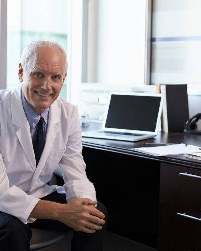 Portrait Of Doctor Wearing White Coat In Office